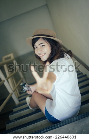 Woman photographer holding film camera on the stairs, Color effect