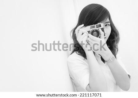Woman photographer holding film camera on white background, Black & White image - stock photo