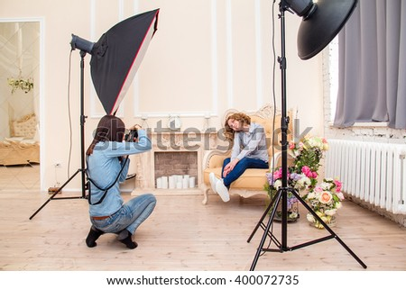 Woman photographer in a studio making portrait photo shoot session for young woman. Softbox flash and other impulse light equipment in the interior of photographic studio - stock photo