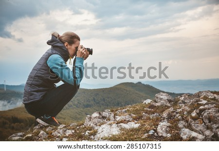 Woman photographer is taking a picture of mountain landscape - stock photo