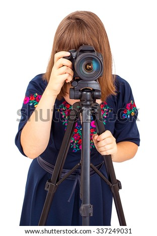 Woman photographer looking into the camera lens on a tripod isolated on white background - stock photo
