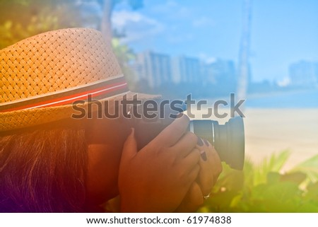 Woman photographer shooting with her digital camera outdoors in a tropical area with abstract color glow. - stock photo