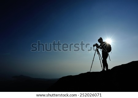 woman photographer taking photo on sunset mountain peak - stock photo