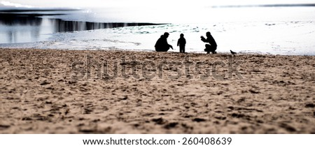Woman photographing her child and husband on the beach. Family silhouettes on the beach in The morning. Copy space. . Extreme Wide Shot. EWS - stock photo
