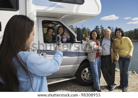 Woman Photographing Her Family with Cell Phone Camera - stock photo