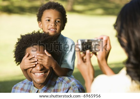 Woman photographing husband and son in park with digital camera. - stock photo
