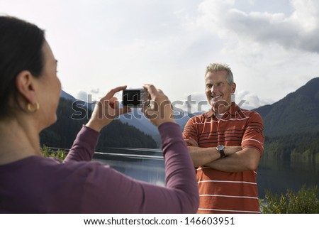 Woman photographing mature man with mountains in the background - stock photo