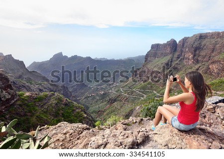 Woman photographing mountains while sitting on cliff. Young female is using smart phone to click picture of beautiful nature. Rear view tourist visiting Tenerife, Masca Valley, Canary Islands, Spain. - stock photo