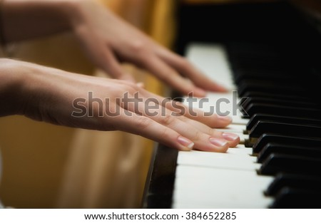 Woman pianist plays a piano