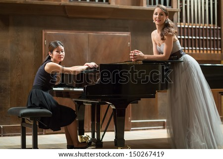 Woman pianist sits at the piano and beautiful singer stands next - stock photo