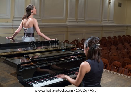 Woman pianist sits at the piano and beautiful singer stands next in empty concert hall - stock photo