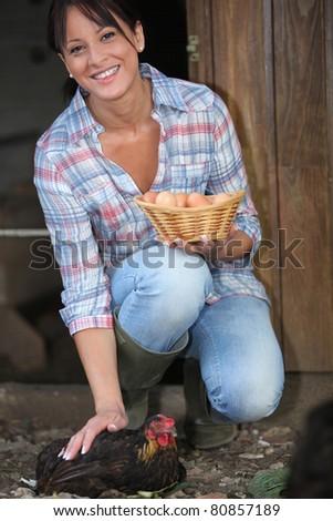 woman picking eggs - stock photo