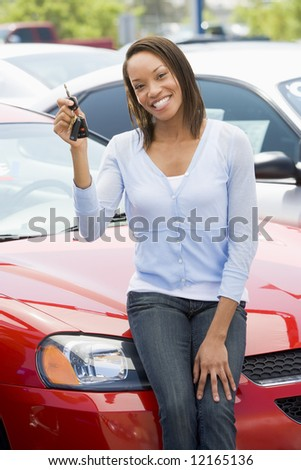 Woman picking up new car from lot - stock photo