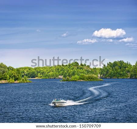 Woman piloting motorboat on lake in Georgian Bay, Ontario, Canada - stock photo