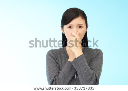 Woman pinches her nose - stock photo