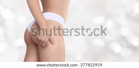 Woman pinches her thigh to control cellulite isolated on blurred light background - stock photo