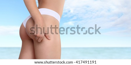 Woman pinches her thigh to control cellulite isolated on sea and sky background - stock photo