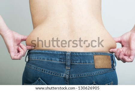 Woman pinching fat from her waist. Back shot - stock photo