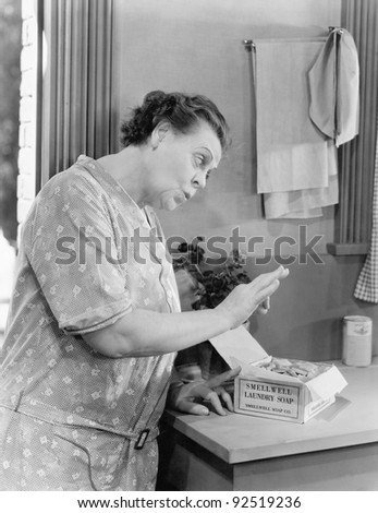 Woman pinching laundry soap from a box