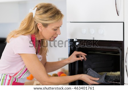 woman placing a cake in the oven