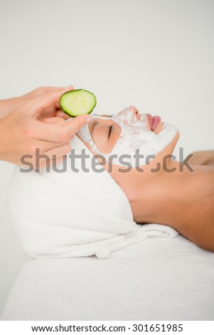 Woman placing cucumber on patient eye at the health spa
