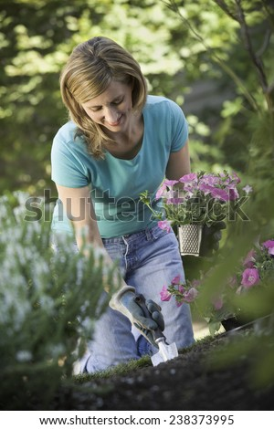 Woman Planting Flowers in Yard - stock photo