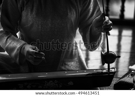 "Woman play a typical vietnamese monochord musical instrument : the "" dan bau "" . Black and white picture"