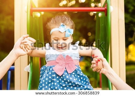 Woman play with girl on the playground and feels happy - stock photo