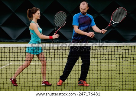 Woman player and her coach practicing on a tennis court - stock photo