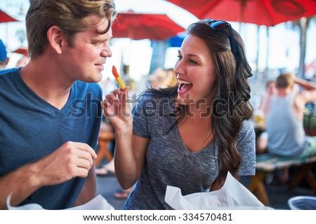 woman playfully feeding her boyfriend a french fry - stock photo