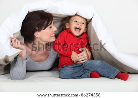 Woman playing a hiding game with her child - stock photo