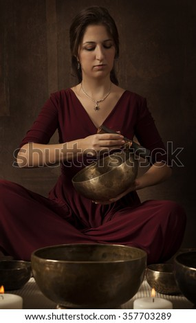 Woman playing a Tibetan bowl, traditionally used to aid meditation in Buddhist cultures - stock photo