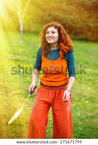 woman playing badminton in the park, sport in sunlight. - stock photo