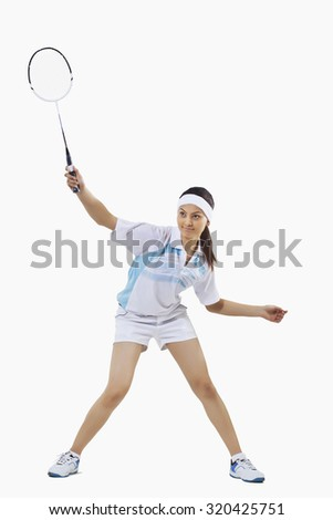 Woman playing badminton isolated over gray background