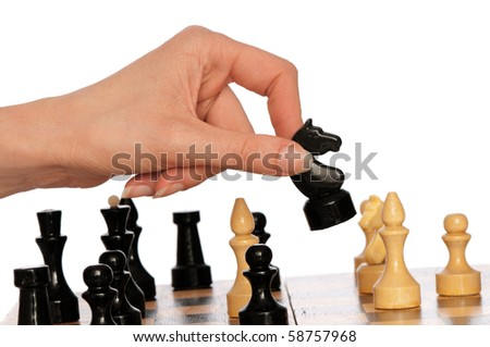 Woman playing chess and making black knight's move - stock photo