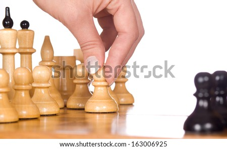woman playing chess, and shows the hand of chess pieces - stock photo