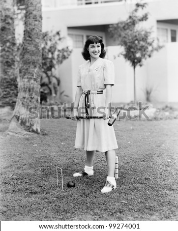 Woman playing croquet in the yard - stock photo