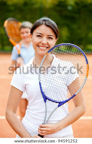 Woman playing doubles at tennis and smiling