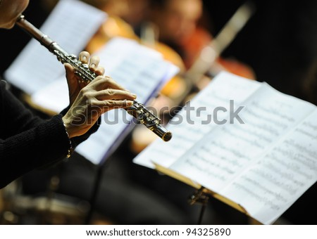 Woman playing flute during a classical concert music - stock photo