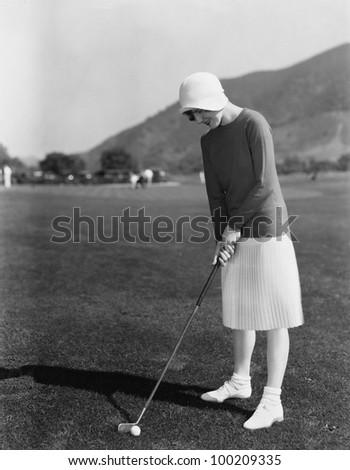 Woman playing golf - stock photo