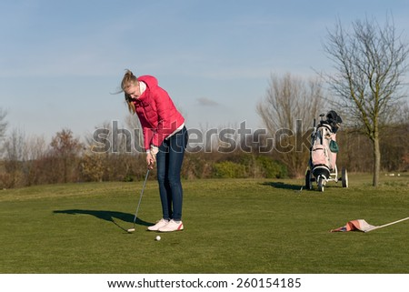Woman playing golf lining up a putt on the green with her golf cart and clubs visible behind on a sunny blue sky day - stock photo