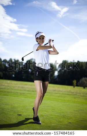 Woman playing golf on field  - stock photo