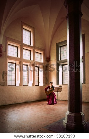 Woman playing guitar in castle. A woman playing a guitar while sitting in a large open room in Marlbork Castle, Poland. - stock photo