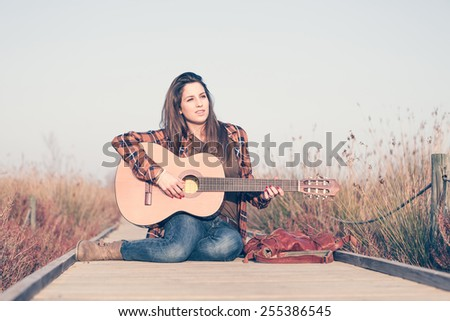 Woman playing guitar on a catwalk in the field enjoying nature - stock photo