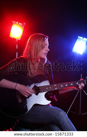 woman playing guitar on stage - stock photo