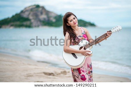 Woman playing guitar on the beach - stock photo