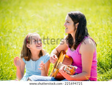 Woman playing guitar to her child outdoor in nature on sunny day - stock photo