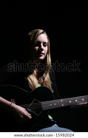 woman playing guitar with dramatic lighting - stock photo