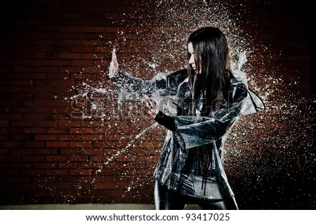 Woman Playing In Rain with water droplets spraying all around her as she tries to ward it off with her hands. - stock photo