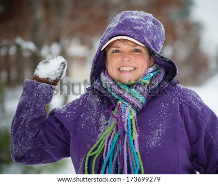 Woman playing in snow throwing snowball - stock photo